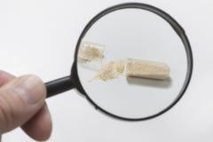 Het inspecteren van gebroken antibiotische capsule met vergrootglas Stock Fotografie