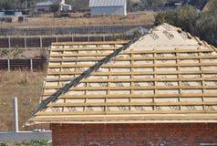 Het installeren van houten daksparren, eaves, waterdicht makend membraan, logboeken en hout op de hoek van het huisdak stock foto