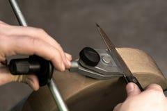Het installeren van het mes met de houder op de slijpsteen royalty-vrije stock foto