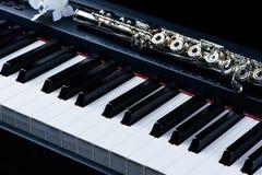 Het instrumentenfluit van de jazzmuziek en dichte omhooggaand van het pianotoetsenbord met bloem Stock Fotografie