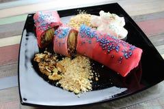 Het interesseren rolde pannekoek met chocoladeroom en banaan wordt gevuld en koekjeskruimeltaarten op de zwarte plaat met slagroo stock foto's