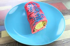 Het interesseren rolde pannekoek met chocoladeroom en banaan wordt gevuld en koekjeskruimeltaarten op de zwarte plaat met slagroo stock fotografie