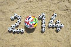 Het internationale Bericht van 2014 in Zand met de Ballen van het Voetbalvoetbal Royalty-vrije Stock Afbeeldingen