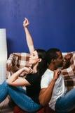 Het internationale paar geniet van thuis luistert muziek Stock Afbeeldingen