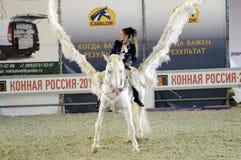 Het internationale Paard toont Vrouwelijke ruiter op een wit paard pegasus De witte jockey van de Vleugelsvrouw in blauwe kleding Stock Foto's