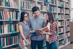 Het internationale trio concentreerde slimme jonge studenten bookw stock foto's