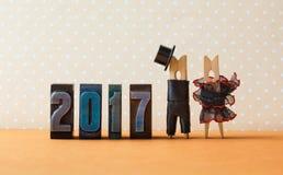 het jaar van 2017 in de affiche van de liefdepartij Hoed van het bruidegom de zwarte kostuum, bruid zwarte rode kleding Wasknijpe Royalty-vrije Stock Foto's