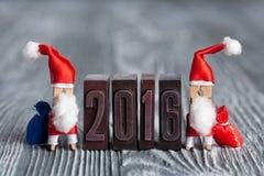 het jaar van 2016 De Kaart van de Kerstmisuitnodiging wasknijper Santa Claus met zakken van giften Royalty-vrije Stock Afbeeldingen