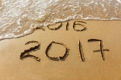 het jaar van 2016 en van 2017 op strandoverzees die wordt geschreven Stock Afbeelding
