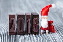 het jaar van 2016 geschreven met gekleurd uitstekend letterzetsel Kerstmisconcept - wasknijper Santa Claus met een zak van giften Stock Afbeelding
