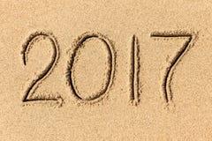 het jaar van 2017 op het strandzand dat wordt geschreven Stock Afbeelding