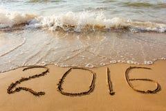 het jaar van 2016 op zandig strand wordt geschreven dat Stock Afbeelding