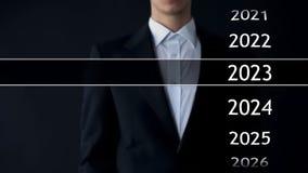 het jaar van 2023 in virtueel archief, zakenman bij de achtergrondinzameling van statistieken royalty-vrije stock afbeeldingen