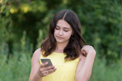 het 14 jaarmeisje leest sms op telefoon Royalty-vrije Stock Foto's
