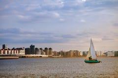 Het jacht die op de golven van de overzeese baai op de achtergrond varen royalty-vrije stock afbeelding