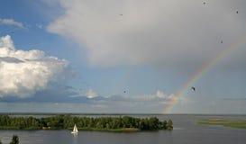 Het jacht vaart op de riviermening van een mooie hemel en een regenboog op de achtergrond royalty-vrije stock fotografie