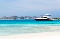 Het jacht van de luxe door het strand Stock Foto