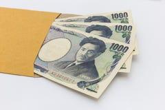 Het Japanse bankbiljet 1.000 Yen in bruine envelop voor geeft en het bedrijfssucces en winkelen Royalty-vrije Stock Fotografie