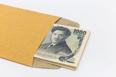 Het Japanse bankbiljet 1.000 Yen in bruine envelop voor geeft en het bedrijfssucces en winkelen Royalty-vrije Stock Foto's