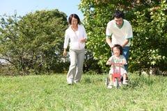 Het Japanse familie spelen in het park Stock Afbeelding
