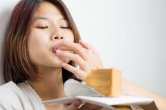 Het Japanse meisje diep geniet door lik van de cake royalty-vrije stock afbeeldingen