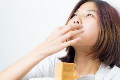 Het Japanse meisje diep geniet door lik van de cake op haar vinger royalty-vrije stock foto