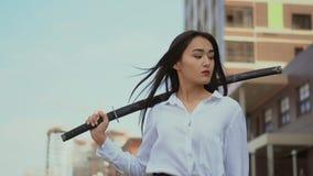 Het Japanse meisje onderzoekt camera, die zich in wind met traditioneel samoeraienzwaard bevinden stock footage