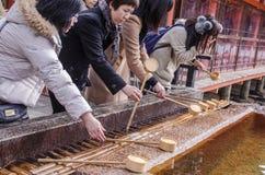 Het Japanse mensen wassen dient een tempel in Stock Foto