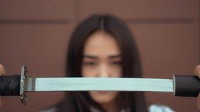 Het Japanse schoolmeisje trekt katana van schede met ernstig gezicht Confidenddame stock videobeelden