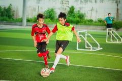 Het jong geitjevoetbal geniet van speel een voetbal stock foto's