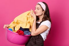 Het jonge aanbiddelijke het glimlachen huisvrouw lopen met roze bassin in één hand, die veel wasserij hebben, kijkt opgetogen, sl royalty-vrije stock foto