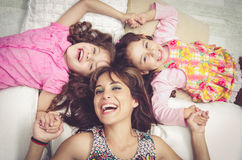 Het jonge aanbiddelijke Spaanse zusters en moeder liggen Stock Foto