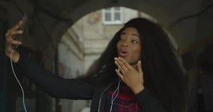 Het jonge aantrekkelijke Afrikaanse meisje neemt grappige selfies via de mobiele telefoon Zij verzendt luchtkussen, het tonen stock footage