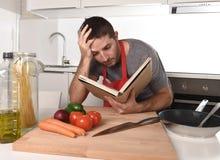 Het jonge aantrekkelijke boek van het de lezingsrecept van de mensen thuis keuken in spanning Royalty-vrije Stock Afbeeldingen