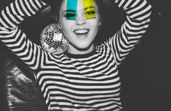 Het jonge aantrekkelijke emotionele meisje bij partij in de holding van de strookkleding en kijkt door de kleurrijke plastic film stock foto