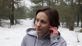 Het jonge Aantrekkelijke Kaukasische meisje brengt haar oortelefoons aan alvorens in het sneeuwpark in de winter te lopen Dicht e stock footage