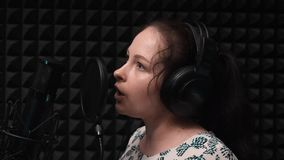 Het jonge aantrekkelijke lied van de vrouwenopname bij professionele vocale studio Het leuke meisje zingt lied bij muziekstudio O stock videobeelden