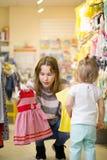 Het jonge aantrekkelijke mamma met weinig dochter probeert op kleren Stock Afbeeldingen