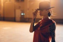 Het jonge, aantrekkelijke meisje in een hoed stelt aan de camera bij nacht stock foto