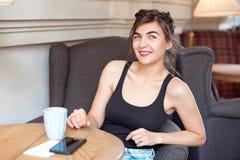 Het jonge aantrekkelijke meisje in een zwarte T-shirt en jeans zit in een koffie bij de lijst en drinkt koffie in een uitstekende royalty-vrije stock fotografie