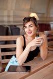 Het jonge aantrekkelijke meisje in een zwarte T-shirt en jeans zit in een koffie bij de lijst en drinkt koffie in een uitstekende royalty-vrije stock foto