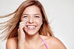 Het jonge aantrekkelijke meisje glimlacht en wrijft zijn neus op room royalty-vrije stock foto