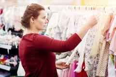 Het jonge aantrekkelijke meisje kiest kleren in de wandelgalerij Probeer op kleren op de hanger in de opslag Het winkelen kleren  royalty-vrije stock fotografie