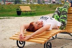 Het jonge aantrekkelijke meisje ligt op een chaise zitkamer op het stadsstrand en de mooie glimlachen Stock Afbeeldingen