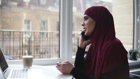 Het jonge aantrekkelijke meisje van onherkenbare nationaliteit met hijab op haar hoofd spreekt aan iemand op de telefoon terwijl  stock footage
