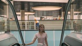 Het jonge aantrekkelijke meisje verschijnt op roltrap in wandelgalerij, het winkelen concept, manierconcept stock videobeelden