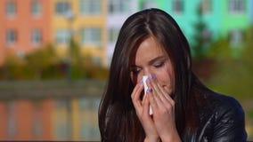 Het jonge aantrekkelijke meisje, ving een koude op de straat, afveegt haar neus met een servet stock videobeelden