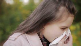 Het jonge aantrekkelijke meisje, ving een koude op de straat, afveegt haar neus met een servet stock footage