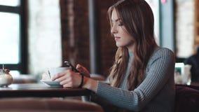 Het jonge aantrekkelijke meisje zit in een comfortabele koffie en gebruikt een mobiele telefoon stock video