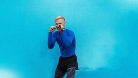 Het jonge aantrekkelijke mens in dozen doen op blauwe achtergrond royalty-vrije stock foto's